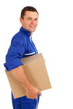 Delivery man in blue overalls with box Royalty Free Stock Image