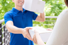 Delivery man in blue uniform delivering parcel box to a woman. Smiling delivery man in blue uniform delivering parcel box to a woman - courier service concept stock image