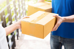 Delivery man in blue uniform handing parcel box to recipient. Courier service concept Stock Photos