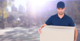 Delivery man with box against blurry street with flare. Digital composite of Delivery man with box against blurry street with flare Stock Photos