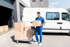 Delivery man with box. And cart next to van Stock Photo