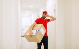 Delivery man with box and clipboard in corridor Royalty Free Stock Photography