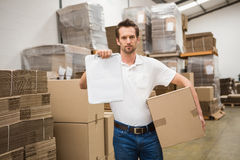 Delivery man with box and clipboard in warehouse Royalty Free Stock Photo