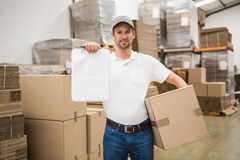 Delivery man with box and clipboard in warehouse Royalty Free Stock Images