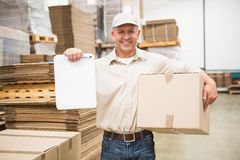 Delivery man with box and clipboard in warehouse Royalty Free Stock Photography