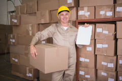 Delivery man with box and clipboard in warehouse Stock Images