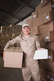 Delivery man with box and clipboard in warehouse Royalty Free Stock Photos
