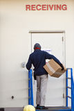 Delivery man with box deliver cargo to receiveng door Stock Images