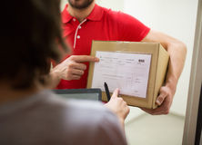Delivery man with box, tablet pc and customer Royalty Free Stock Image