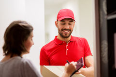 Delivery man with box and tablet pc at customer Stock Photo