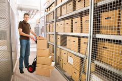 Delivery man with boxes on hand truck in warehouse. Portrait of delivery man with stacked cardboard boxes on hand truck at warehouse Stock Photography