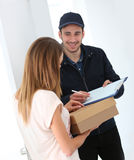 Delivery man bringing the package to woman Stock Photos