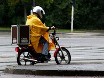 Delivery Man Can Not Be Stopped By Rain. Delivery man on his bike in the rain Stock Images