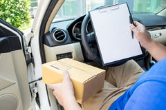 Delivery man with cardboard box checking document list In van an Stock Image