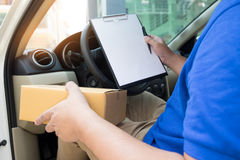 Delivery man with cardboard box checking document list In van an Stock Photos