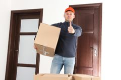 Delivery man with cardboard box stock photos