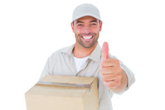 Delivery man with cardboard box gesturing thumbs up Stock Images