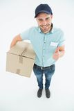 Delivery man with cardboard box gesturing thumbs up Royalty Free Stock Images