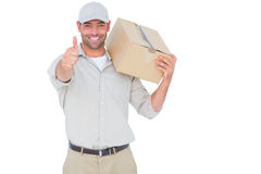 Delivery man with cardboard box gesturing thumbs up Stock Photos