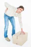 Delivery man with cardboard box suffering from back ache Stock Photos