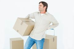 Delivery man with cardboard box suffering from back ache Stock Photography