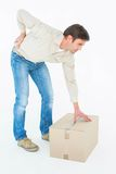 Delivery man with cardboard box suffering from backache Stock Photos