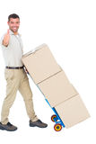 Delivery man with cardboard boxes gesturing thumbs up Stock Image