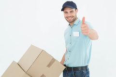 Delivery man with cardboard boxes gesturing thumbs up Stock Photos