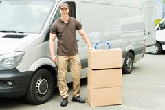 Delivery Man With Cardboard Boxes. Happy Delivery Man With Cardboard Boxes On Trolley Stock Photo