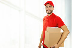 Delivery man with cardboard boxes standing in office Stock Image