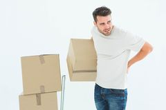 Delivery man with cardboard boxes suffering from backach Stock Photography