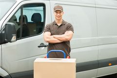 Delivery Man With Cardboard Boxes On Trolley. Young Happy Delivery Man With Cardboard Boxes On Trolley In Front Of Van Stock Photo