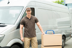 Delivery Man With Cardboard Boxes On Trolley. Young Happy Delivery Man With Cardboard Boxes On Trolley In Front Of Van Royalty Free Stock Photography
