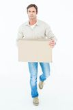 Delivery man carrying cardboard box while walking Royalty Free Stock Photography