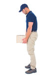 Delivery man carrying heavy package on white background. Full length side view of delivery man carrying heavy package on white background Stock Image