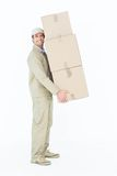 Delivery man carrying stacked cardboard boxes Stock Image