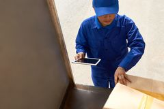 Delivery man checking boxes. Delivery man with digital tablet checking boxes in his truck royalty free stock photography