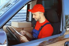 Delivery man checking list with parcels. Delivery man checking list in car with parcels Royalty Free Stock Image