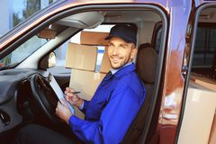 Delivery man checking list with parcels. Delivery man checking list in car with parcels stock photography