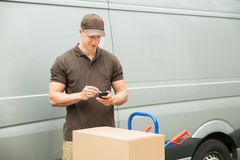 Delivery Man Checking List On Mobile Phone Royalty Free Stock Photography