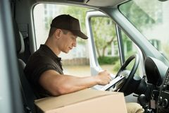 Delivery Man Checking List In Van. Young Delivery Man Checking List On Clipboard In Van Stock Image