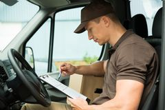 Delivery Man Checking List In Van. Young Delivery Man Checking List On Clipboard In Van Stock Images