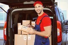 Delivery man checking packages. From car royalty free stock images