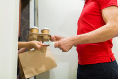 Delivery man with coffee and food at customer home Royalty Free Stock Photos