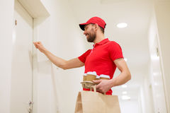 Delivery man with coffee and food knocking on door Royalty Free Stock Images