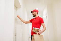 Delivery man with coffee and food knocking on door Royalty Free Stock Image