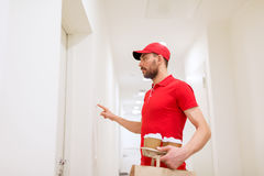 Delivery man with coffee and food ringing doorbell Stock Photo