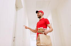 Delivery man with coffee and food ringing doorbell Stock Images