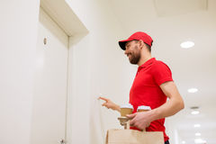 Delivery man with coffee and food ringing doorbell Stock Photos