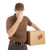 Delivery Man with Cold. Delivery man suffering with a cold or flu on the job.  Isolated on white Royalty Free Stock Photo